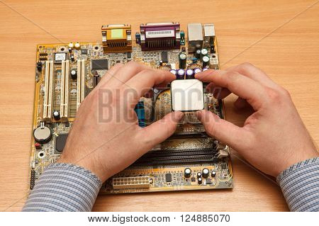 Repairman Inserted Cpu Into The Socket On The Motherboard. Close-up.