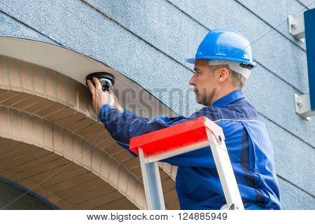 Male Technician Installing Camera Standing On Stepladder
