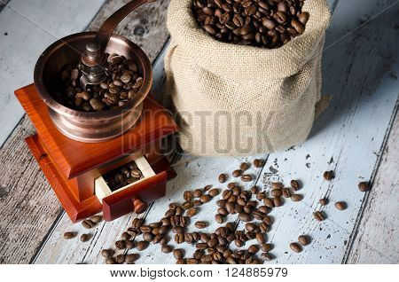 Coffee grinder with roasted beans. Vintage mill composition on wooden background