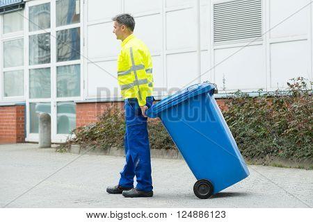 Male Worker Walking With Dustbin On Street