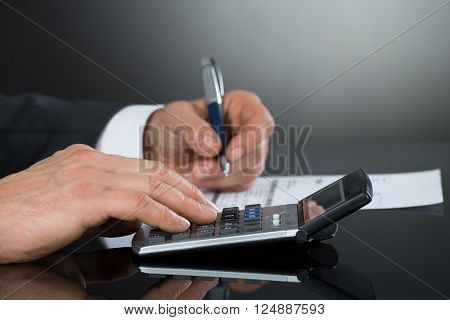 Close-up Of Businessman Using Calculator While Checking Invoice