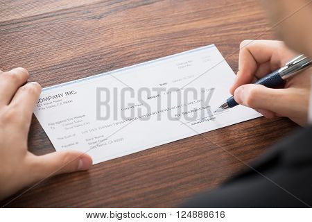 Close-up Photo Of Businessman Filling Blank Cheque