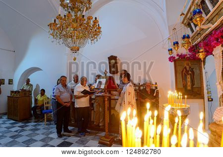 KYTHNOS, GREECE - AUGUST 14, 2014: Chanters and priest performing a liturgy on the eve of Assumption at the church of Panagia Stratolatissa