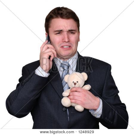 Young Businessman Crying On Cell Phone, Clutching Teddy Bear.