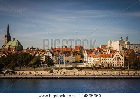 The view of Cathedral Basilica of St. James the Apostle, old town and Ducal Castle, and the Oder river in Szczecin (Poland) in the sunny day with blue sky