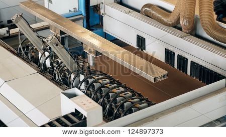 Detail of industrial machinery used for the production of panels and sheets of melamine.