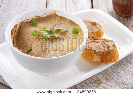 Homemade chicken liver pate on baquette and in white bowl