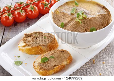 Homemade chicken liver pate on  baquette adn in white bowl with tomatoes