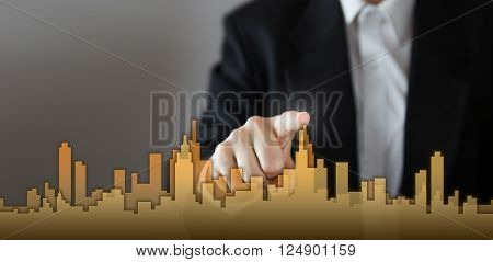 Businessman Activate Growth Process, choosing house, real estate city concept. Skyline Hand pressing the house icon on virtual screen. Business, technology, internet and networking concept. Copy space.