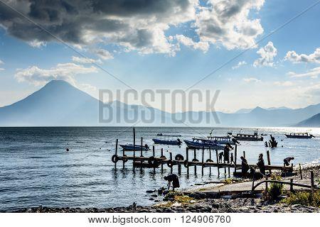 Lake Atitlan, Guatemala - April 3, 2016: Locals by the water in evening light at Lake Atitlan with San Pedro volcano behind in Guatemalan highlands.