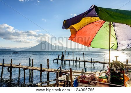 Colorful umbrella on slushie vendor cart in evening light at Lake Atitlan with San Pedro volcano behind in Guatemalan highlands.