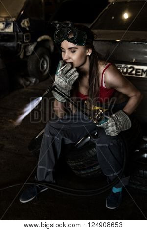 Girl mechanic sitting on a tire with blowpipe and smoking in a garage. car repairs. colorless life concept.