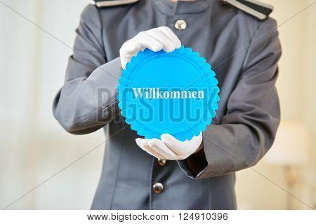 Hotel clerk holding German badge saying