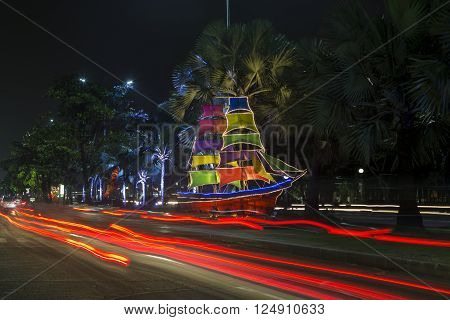 JAKARTA, INDONESIE - MARCH 16, 2016: Scale model sailboats illuminated by colored lights on a street in Jakarta. Ancol beach nearby. INDONESIA