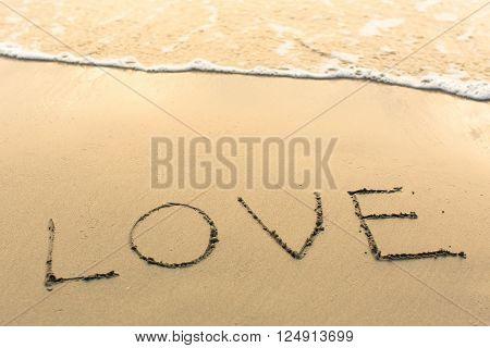 Love - written manually on the texture of sea sand.