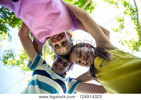 Portrait of happy children forming a huddle in park on a sunny day
