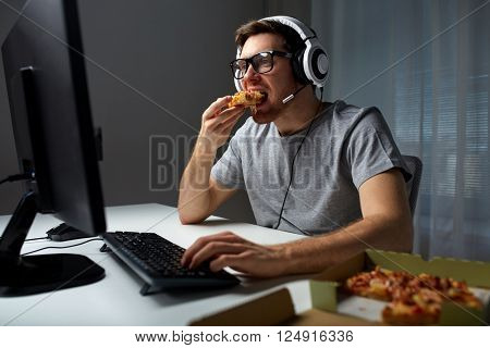 technology, gaming, entertainment, let's play and people concept - young man in headset with pc computer eating pizza while playing game at home and streaming playthrough or walkthrough video poster