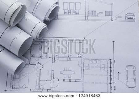 Architect worplace top view. Architectural project, blueprints, blueprint rolls on plans. Construction background. Engineering tools. Copy space.