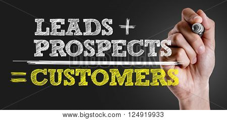 Hand writing the text: Leads + Prospects = Customers