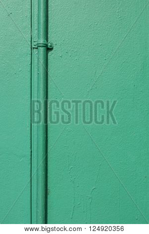 background of pipe line on wall with dark green painting at exterior buliding