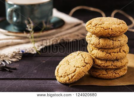 Soft ginger cookies with cracks on a dark wooden background