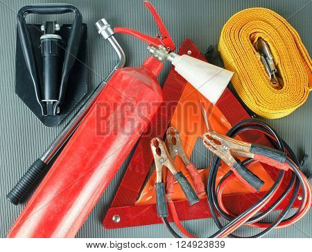 Elements of the essentials for a passenger car. Danger Safety Warning Triangle Sign, towing rope, fire extinguisher, Jumper cable, wheel wrench and shovel.