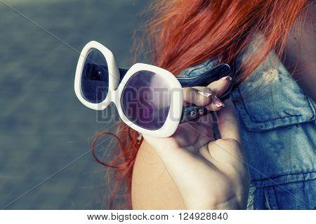 Fashionable sunglasses in redhair women hand closeup.