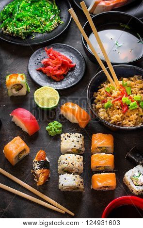 Table served with sushi and traditional japanese food on dark background. Sushi rolls hiyashi wakame miso soup ramen fried rice with vegetables nigiri soy sauce ?hopsticks. Japanese dishes set