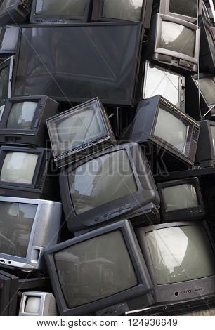old television garbage rubbish TV electronic junk can be recycle. Pile of Obsolete or broken television stacked for disposal Stacked Recycling Electronics. brand names have been removed. Great for recycle and environmental themes.