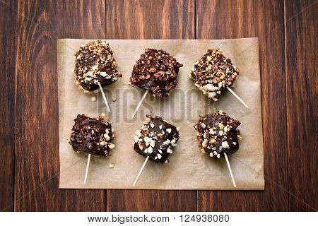 Frozen banana covered with chocolate and peanuts on paper over wooden background top view