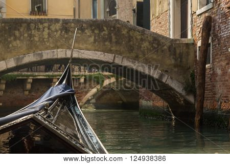 View of a bridge shot from within a gondola on a canal in Venice on a bright sunny day showing the gondola front