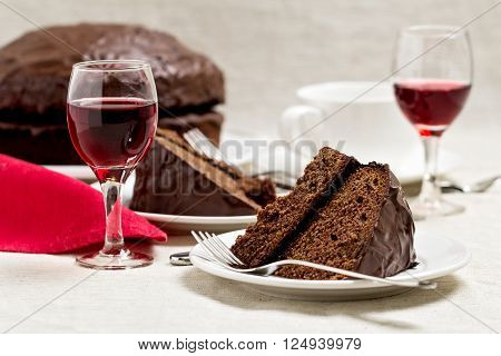 Chocolate cake and glasses of wine. Selective focus.