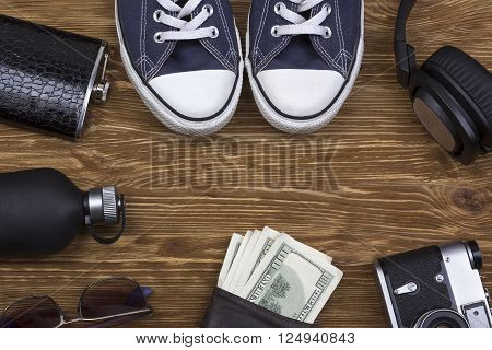 Men's accessories: wallet, headphones, sunglasses, perfume, camera and  sneakers on wooden background