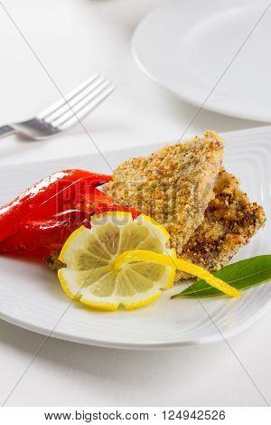 Two small gourmet schnitzels served with fried bell pepper and lemon