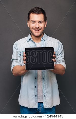 This can help you! Cheerful young man shoving his digital tablet with copy space and looking at camera with smile while standing against grey background