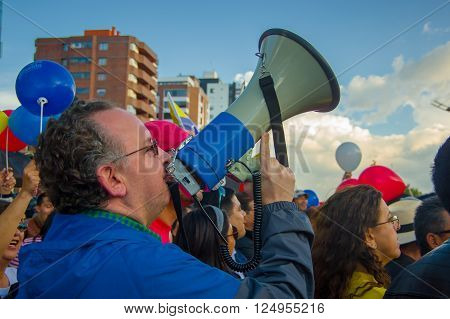 Quito, Ecuador - April 7, 2016: Unidentified opposition protester with megaphone surrounded by people, police and journalists during anti government protests in Shyris Avenue