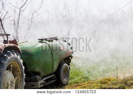 Farmer With Tractor Using A Air Blast Sprayer
