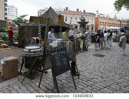 TURKU, ABO FINLAND ON JUNE 29 2013. View of a stand at a Market in the City on June 29, 2013 in Turku, Abo Finland. Unidentified people at a line-up at lunch. Disposed equipment.
