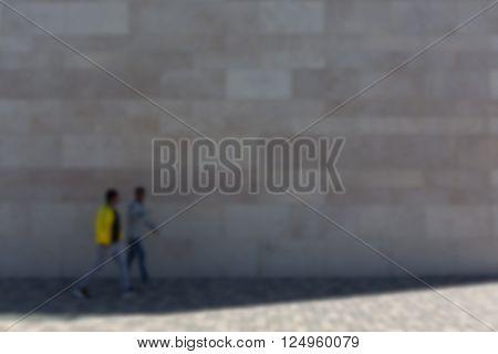 Two men in front of stone wall on sidewalk defocused