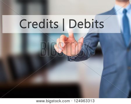 Credits  Debits - Businessman Hand Pressing Button On Touch Screen Interface.