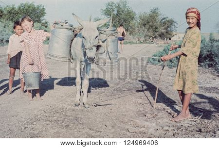 TURKMEN SOVIET SOCIALIST REPUBLIC, USSR- JUNE 25, 1988: Happy kids deliver water from the river to their farmland in Turkmen Soviet Socialist Republic at June 25, 1988