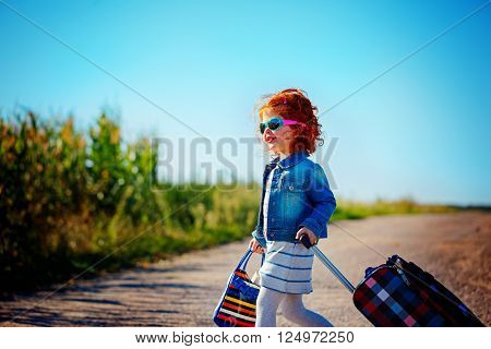 happy and joyful child with suitcases. vacation and trip concept. freedom and wind. girl traveler. summer time