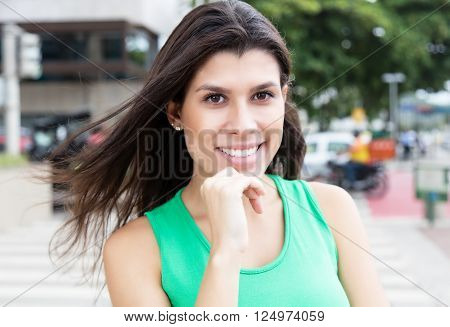 Beautiful woman in a green shirt in city with buildings and traffic onn the street in the background