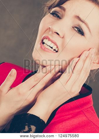 Stress and pain. Face of young painful woman. Female feeling tooth pain ache. Girl touching her mouth teeth by hand.