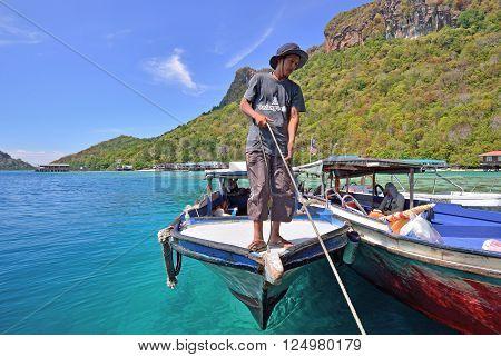 SEMPORNA, MALAYSIA - APRIL 18, 2015 - Unidentified man pulling a passenger boat rope in Bohey dulang Island, near Sipadan Island in Sabah Borneo.