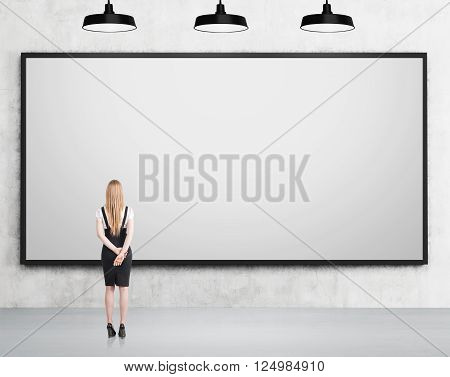 Businesswoman facing large blank whiteboard on concrete wall. Mock up 3D Rendering