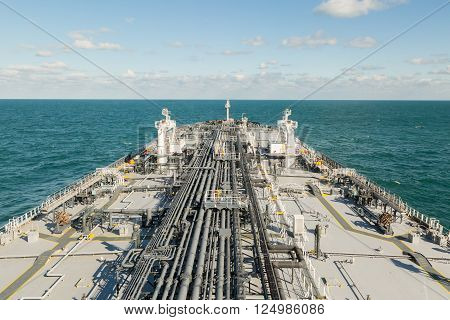 Oil tanker is proceeding in blue ocean under cloudy sky - stock photo.