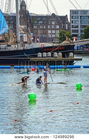 AMSTERDAM, THE NETHERLANDS, AUGUST 20, 2015: Peddling on a surfboard at SAIL Amsterdam 2015, the largest free public sail event in the world.