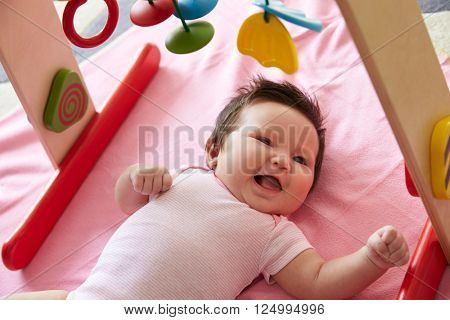 Cute Baby Girl Laying On Pink Blanket Playing With Mobile