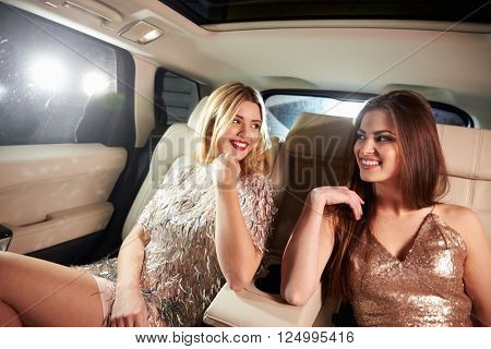 Two women sitting in limo looking at each other, in-car view